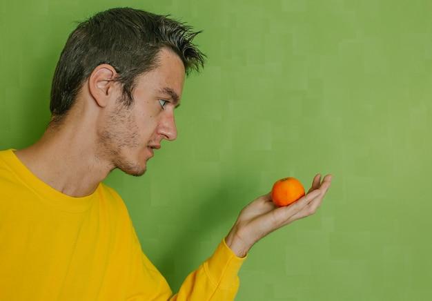 Молодой человек с мандариновым апельсином в руке на зеленом фоне, концепция диеты