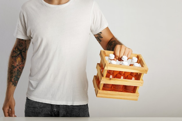 Young man with tattoos wearing jeans and a plain white t-shirt holds a wooden box with six unlabeled bottles of soft drinks