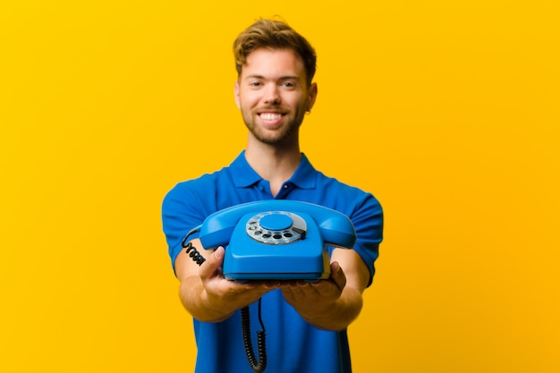 Young man with a telephone against orange