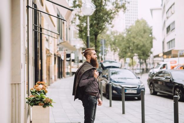 Молодой человек с бородой идет в офис. на спине у вас куртка в классическом стиле