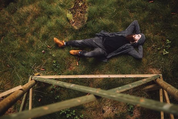 Молодой человек с бородой лежит в лесу.
