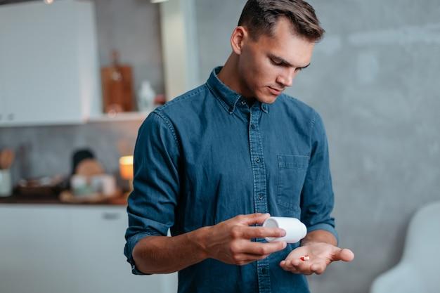 インフルエンザの若い男は家で薬を服用しています