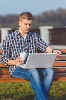 Молодой человек с ноутбуком. концепция удаленной работы на открытом воздухе