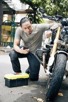 彼の壊れたオートバイを修理するときにスマートフォンのチュートリアルに従うツールボックスを持つ若い男