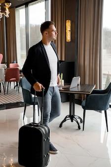 モダンなホテルのロビーの中を歩く旅行かばんを持つ若い男