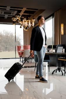 현대 호텔에서 로비 내부 산책 여행 가방을 가진 젊은 남자