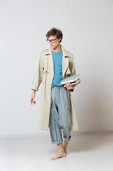 眼鏡をかけ、本を持っているトレンチコートを持つ若い男