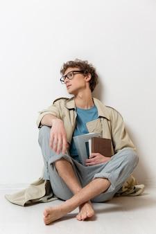 안경을 쓰고 책을 들고 트렌치 코트와 젊은 남자
