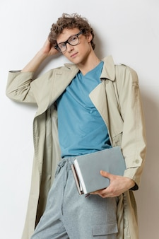 Young man with trench coat wearing glasses and holding books