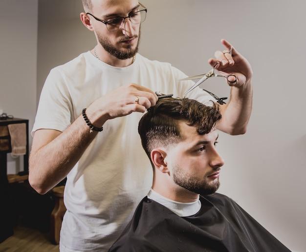 Молодой человек с модной прической в парикмахерской. парикмахерская делает прическу и бороду.