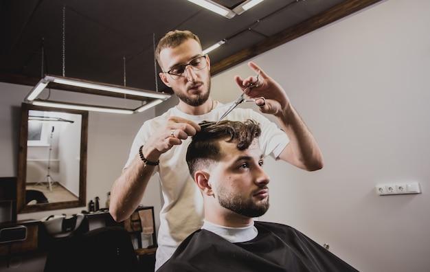 Молодой человек с модной прической в парикмахерской.