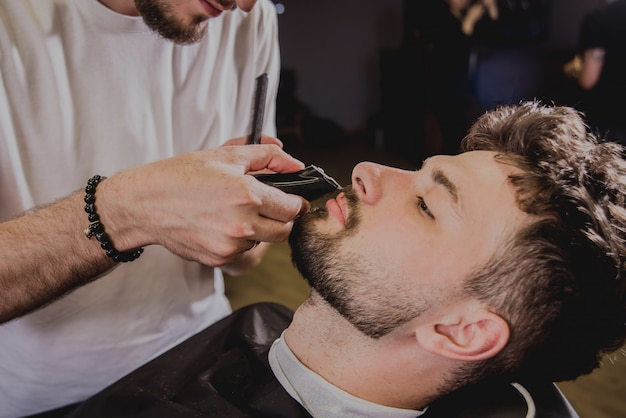 Young man with trendy haircut at barber shop. barber does the hairstyle and beard trim.