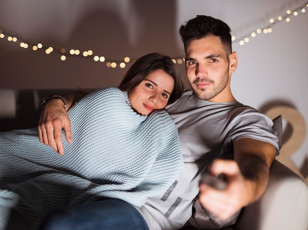 Young man with tv remote hugging woman and lying on sofa