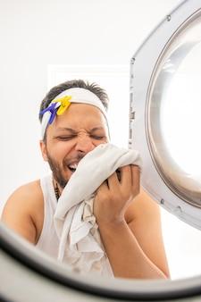 Молодой человек с неопрятной внешностью готовит одежду к стирке в стиральной машине