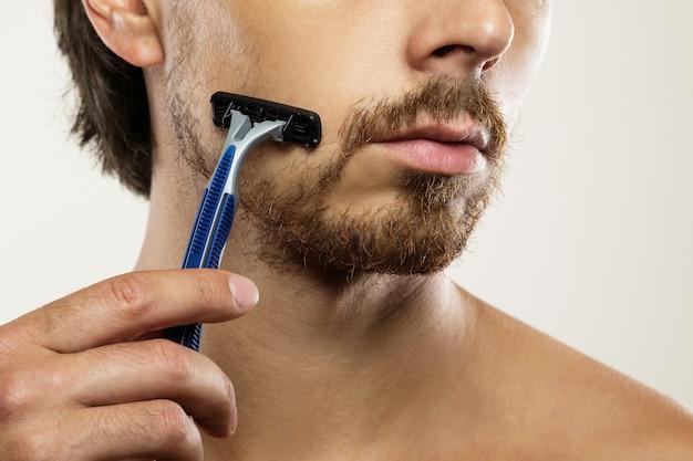 면도 루틴 전에 깔끔하지 못한 수염을 가진 젊은 남자