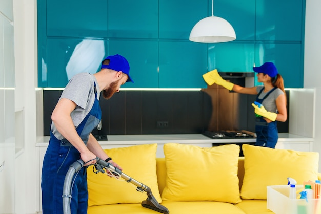 Young man with vacuum cleaner washing with vapor yellow sofa and beautiful woman wipes cuisine furniture.