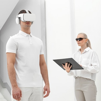 Young man with virtual reality simulator and woman testing
