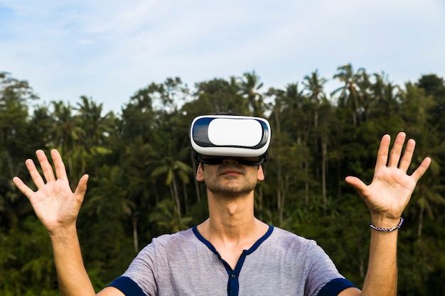 Young man with vr glasses in the tropical forest