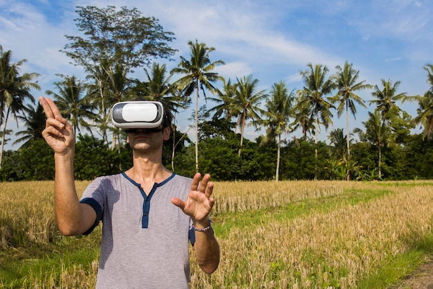 Young man with vr glasses in the tropical rice field