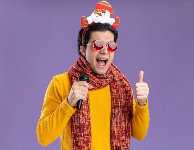 黄色のタートルネックの首の周りに暖かいスカーフとマイクを保持している頭に面白い縁のメガネを持つ若い男は幸せで興奮して紫色の壁の上に立って親指を示しています