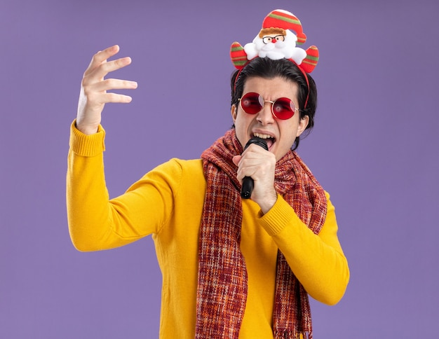 黄色のタートルネックの首の周りに暖かいスカーフとマイクを保持している頭に面白い縁のメガネを持つ若い男幸せで興奮した歌が紫色の壁の上に立っています