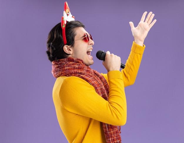 黄色のタートルネックの首の周りに暖かいスカーフと紫色の壁の上に立って幸せで興奮してマイクに向かって叫んで頭に面白い縁のメガネをかけた若い男