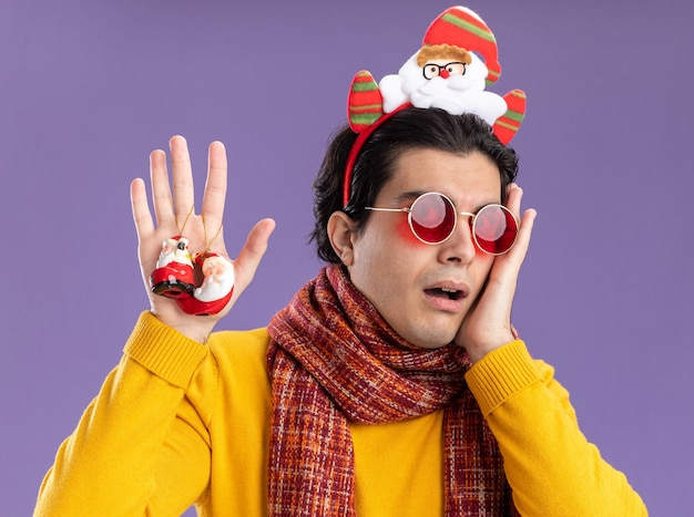 Young man with warm scarf around neck in yellow turtleneck and glasses with funny rim on head holding christmas toys  worried standing over purple wall