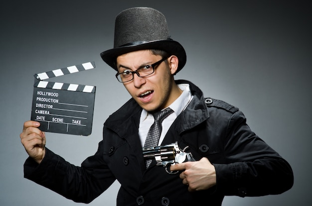 Young man with weapon and clapboard against gray