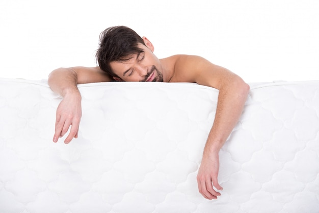 Young man with a white mattress