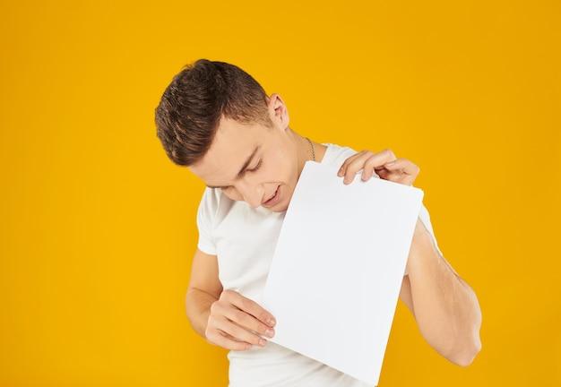 Молодой человек с белым листом бумаги на желтом обрезанном виде копией пространства