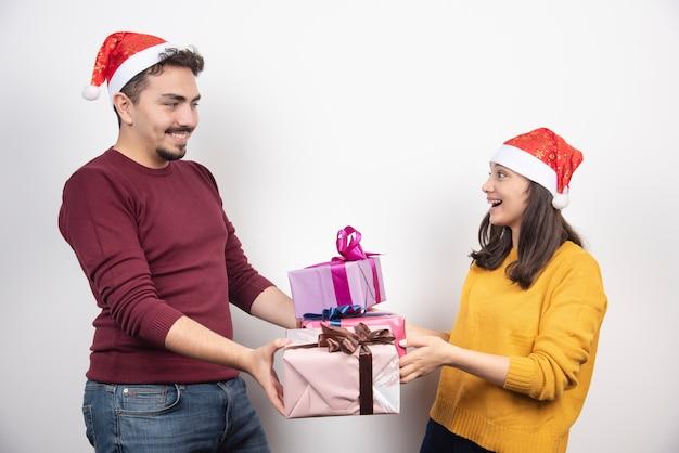 Giovane con la donna in posa con i regali di natale.