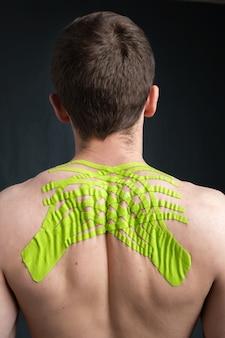 Молодой человек с морщинистой кинезиологической медицинской лентой на спине