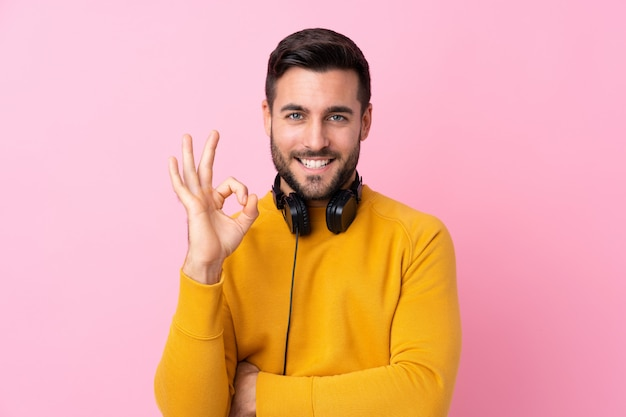Young man with yellow sweater making a gesture ok