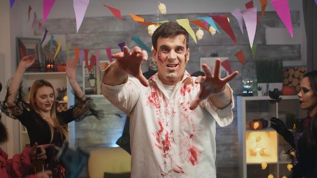 Молодой человек в маскировке зомби празднует хэллоуин со своими друзьями на дикой вечеринке в стиле диско.