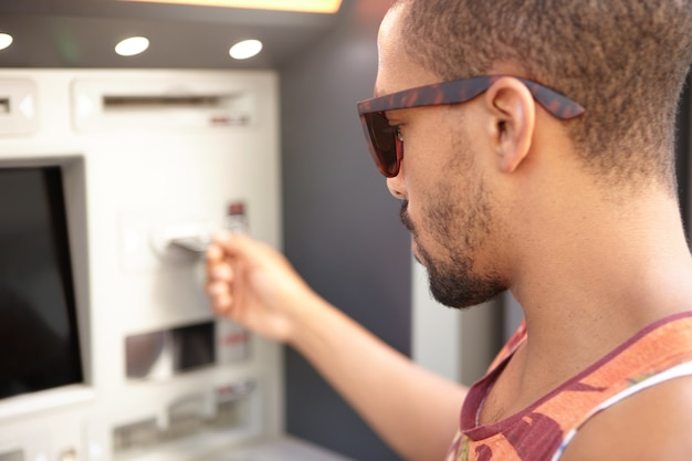Young man withdrawing money from atm