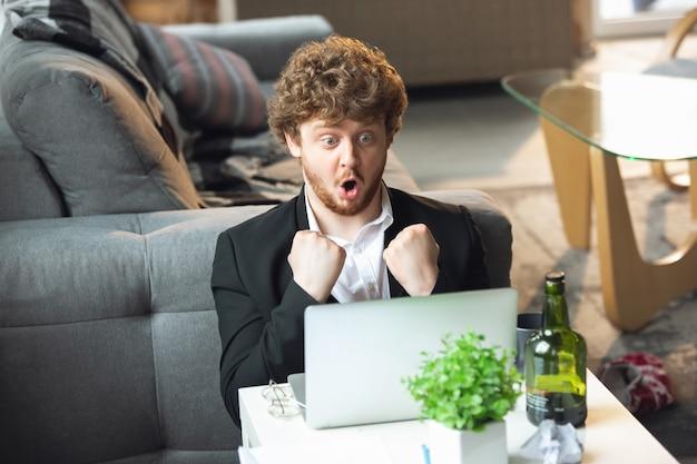 Молодой человек без штанов, но в куртке, работает на удаленном офисе ноутбука во время коронавируса