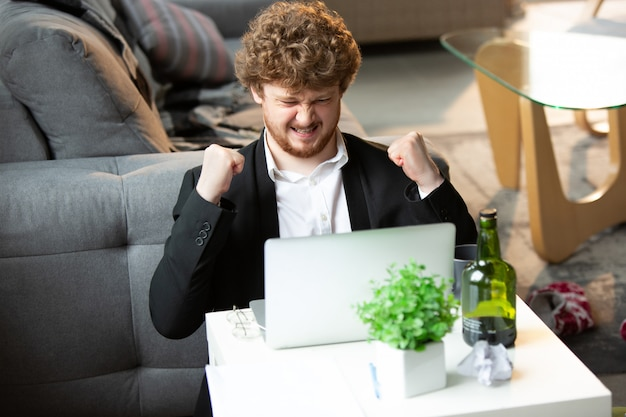 ズボンはないがジャケットはコンピューター、ラップトップに取り組んでいる若い男。