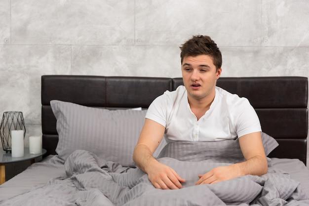 Молодой человек проснулся и сел в стильной кровати в серых тонах, возле тумбочки со свечами в спальне в стиле лофт
