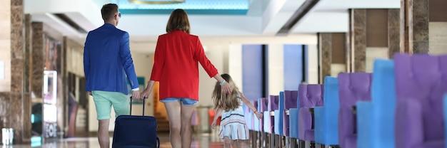 Молодой мужчина, женщина и ребенок с чемоданом идут в вестибюль отеля