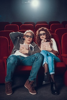Young man and woman are watching horror film