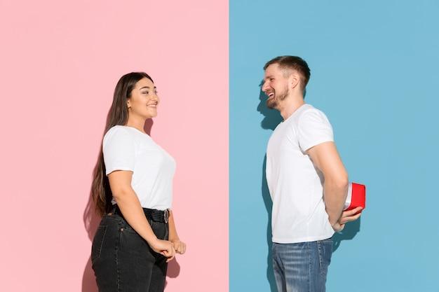 Giovane uomo e donna in abiti casual su sfondo rosa, blu bicolore. uomo che fa un regalo a una donna