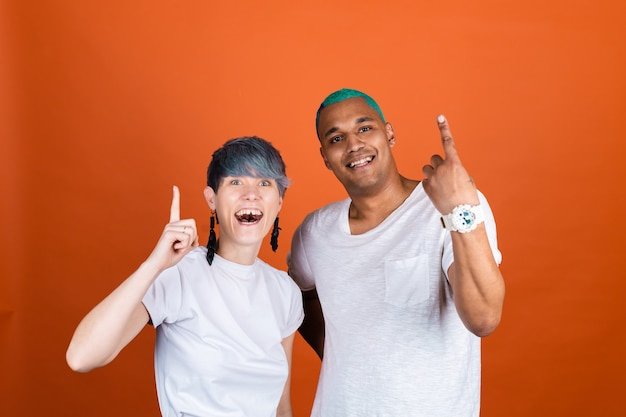 Young man and woman in casual white on orange wall both happy smile  point up with index finger