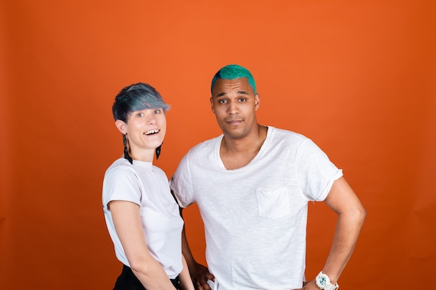 Young man and woman in casual white on orange wall happy and positive emotions