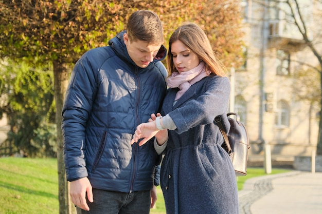 Young man and woman in city, looking at wristwatch