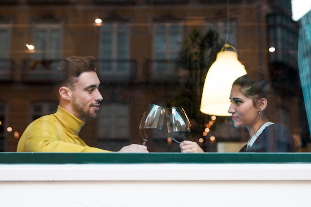Young man and woman clanging glasses of wine in restaurant