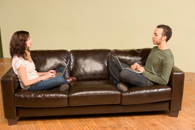 Young man and woman computing on couch