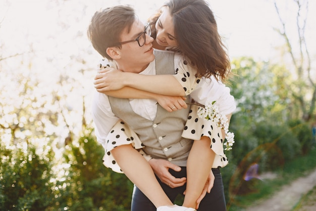 Young man and woman couple in a blooming garden