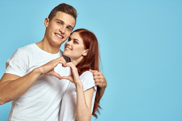 Young man and woman couple in white t-shirts on a light blue background