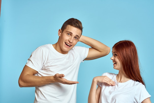 Young man and woman couple in white t-shirts on a light blue