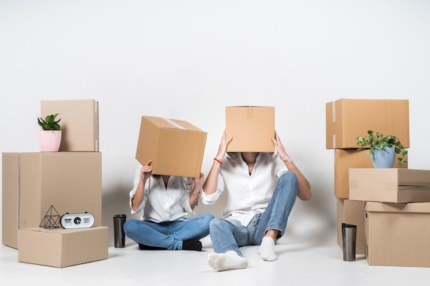 Young man and woman covering heads in boxes